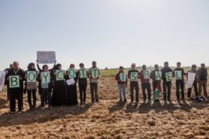 attivisti palestinesi e internazionali con cartelli a sostegno del Boicottaggio, Disinvestimento e Sanzioni (BDS) manifestazione nella zona cuscinetto a Zeitoun, il 9 febbraio 2013. (Foto di Desde Palestina)